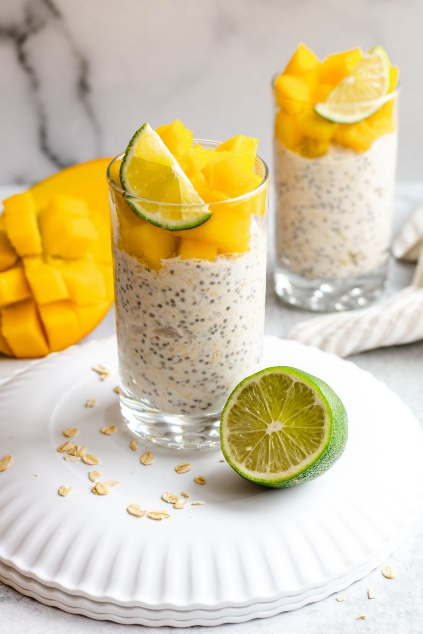 Two cups of mango lime overnight oats with mango chunks and sliced lime on top