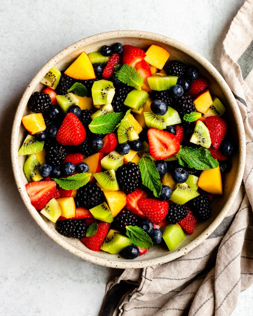 Summer fruit salad in a bowl with gold serving spoon