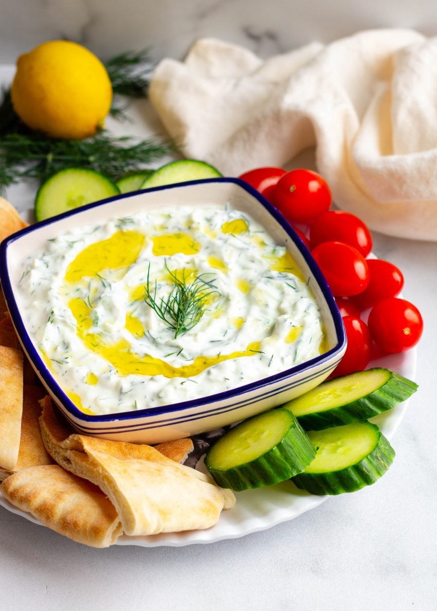 Homemade tzatziki sauce in a bowl surrounded by veggies and pita
