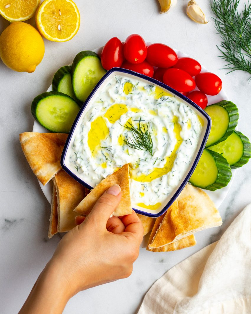Hand dipping pita bread into a bowl of tzatziki with cucumbers, tomatoes, and pita for dipping
