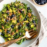 Large bowl of blueberry basil salad with gold serving spoons and a bowl of blueberries on the side