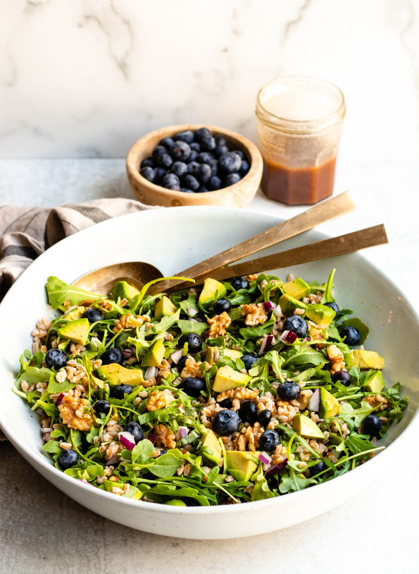 Large bowl of blueberry basil salad with gold serving spoons