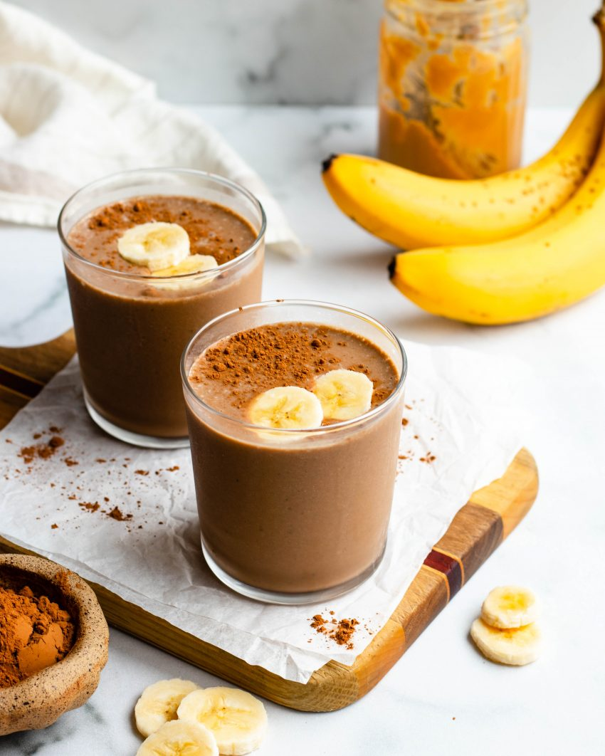 Two glasses of chocolate peanut butter banana smoothie with banana and peanut butter jar in the background