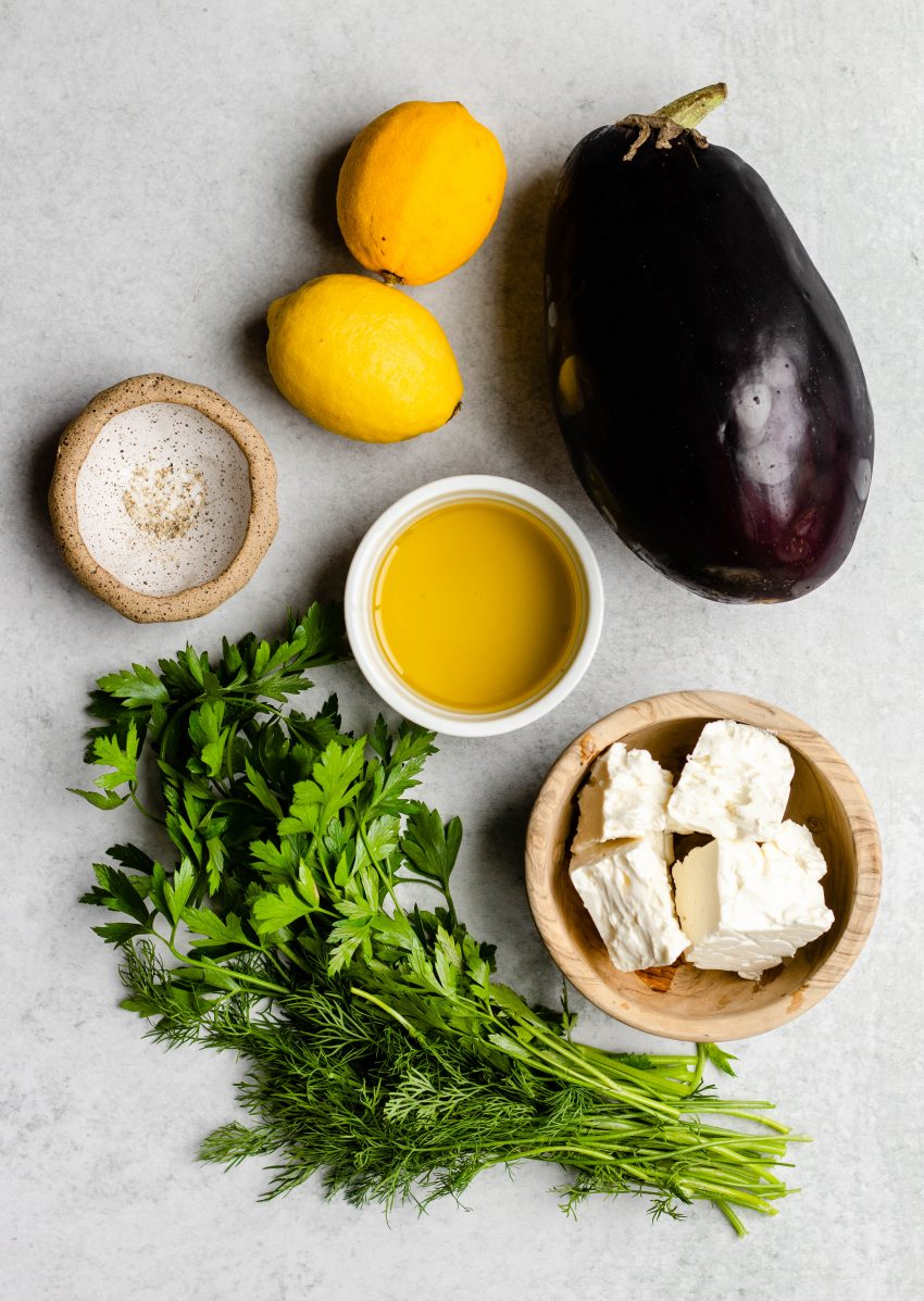 Ingredients for grilled eggplant with feta and herbs on a grey background, some ingredients in small bowls