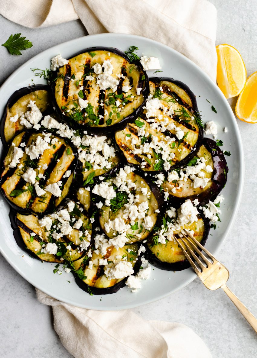 Plate of grilled eggplant slices with feta cheese and herbs with a gold serving fork