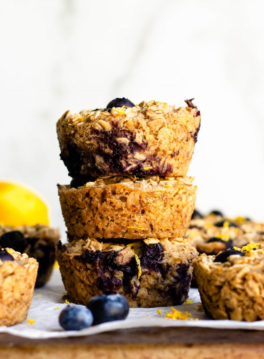 Stack of three lemon blueberry baked oatmeal cups on a cooling rack with parchment paper