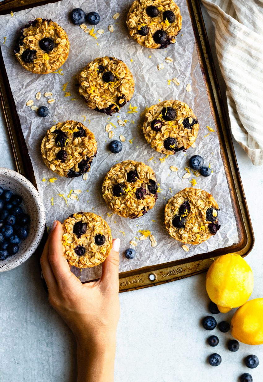 Hand removing a baked oatmeal cup from a tray of lemon blueberry baked oatmeal cups