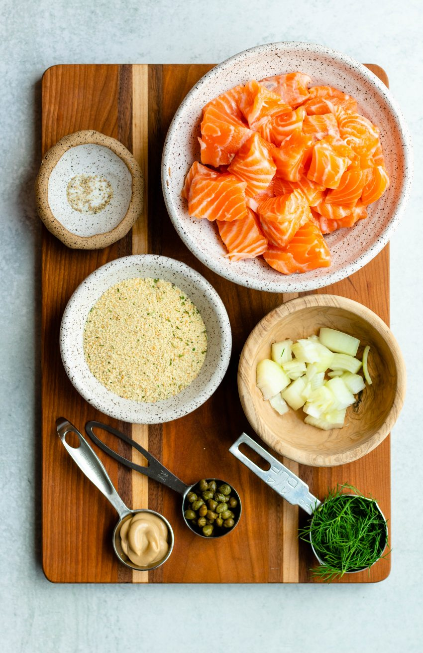 Lemon dill salmon burger ingredients in bowls and measuring utensils on a wooden cutting board
