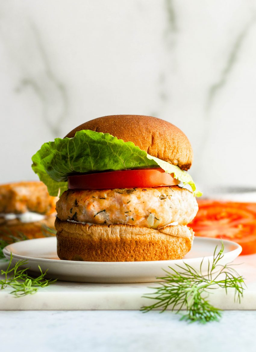 Close up of lemon dill salmon burger on a bun with lettuce and tomato