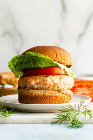 Lemon dill salmon burger on marble board surrounded by ingredients