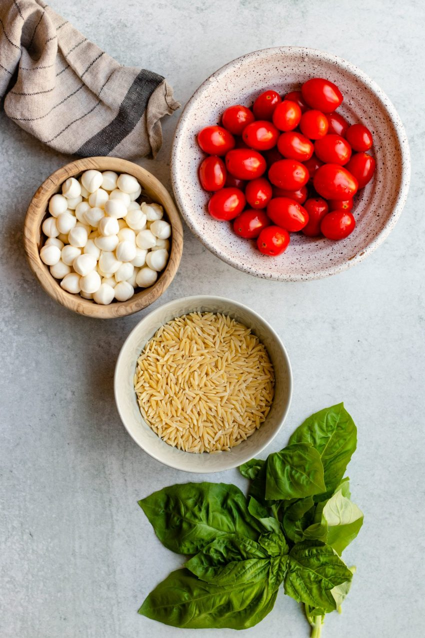 Caprese orzo salad ingredients in bowls on a grey background