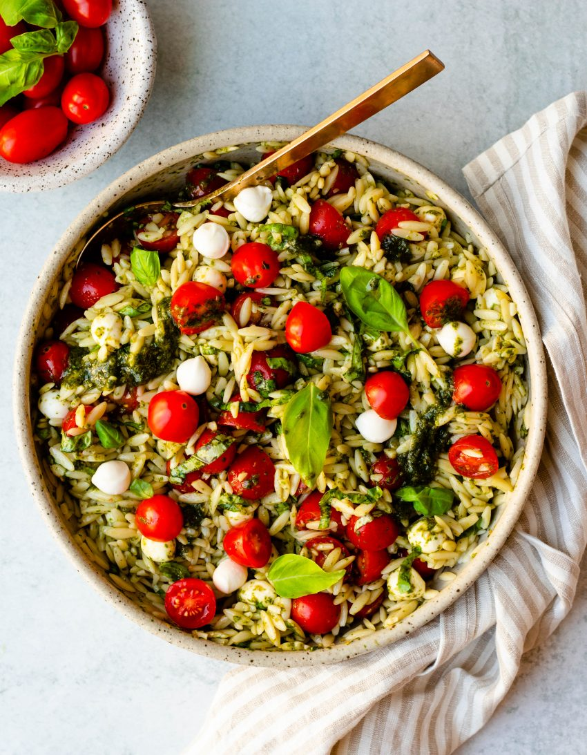 Caprese orzo salad in a bowl with a gold serving spoon