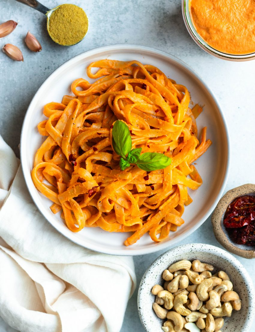 Bowl of creamy sundried tomato pasta with ingredients and sauce surrounding the bowl in small containers