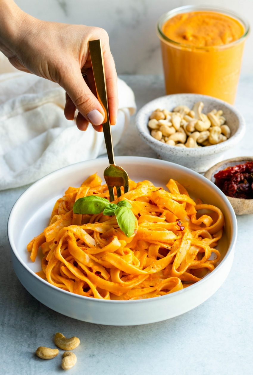 Hand swirling sun dried tomato sauce pasta with a fork from a white bowl with some ingredients behind the bowl