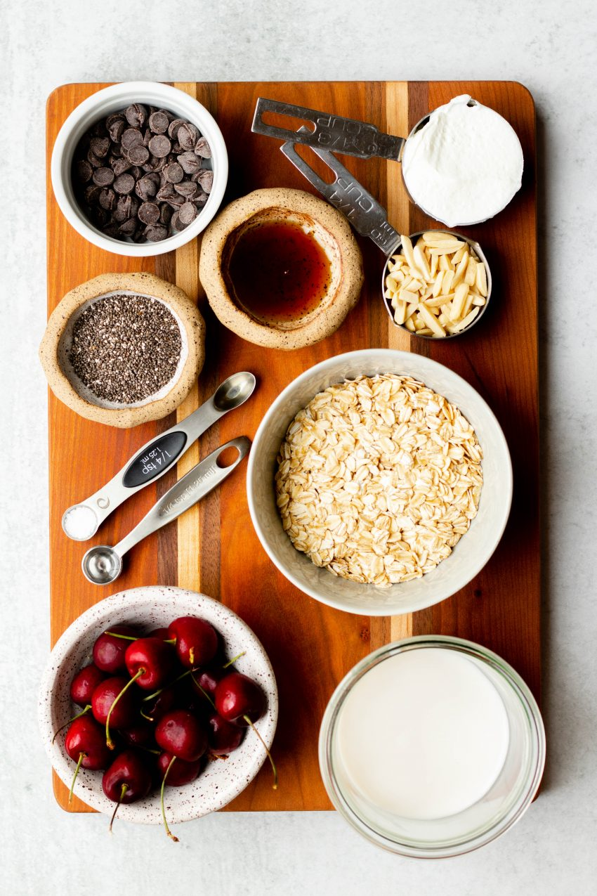 Cherry overnight oats ingredients in bowls and measuring utensils on a wooden cutting board