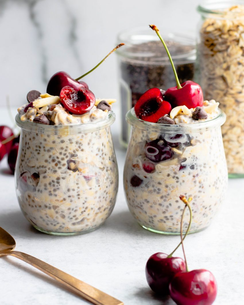 Two jars of cherry overnight oats with jars of ingredients in the background