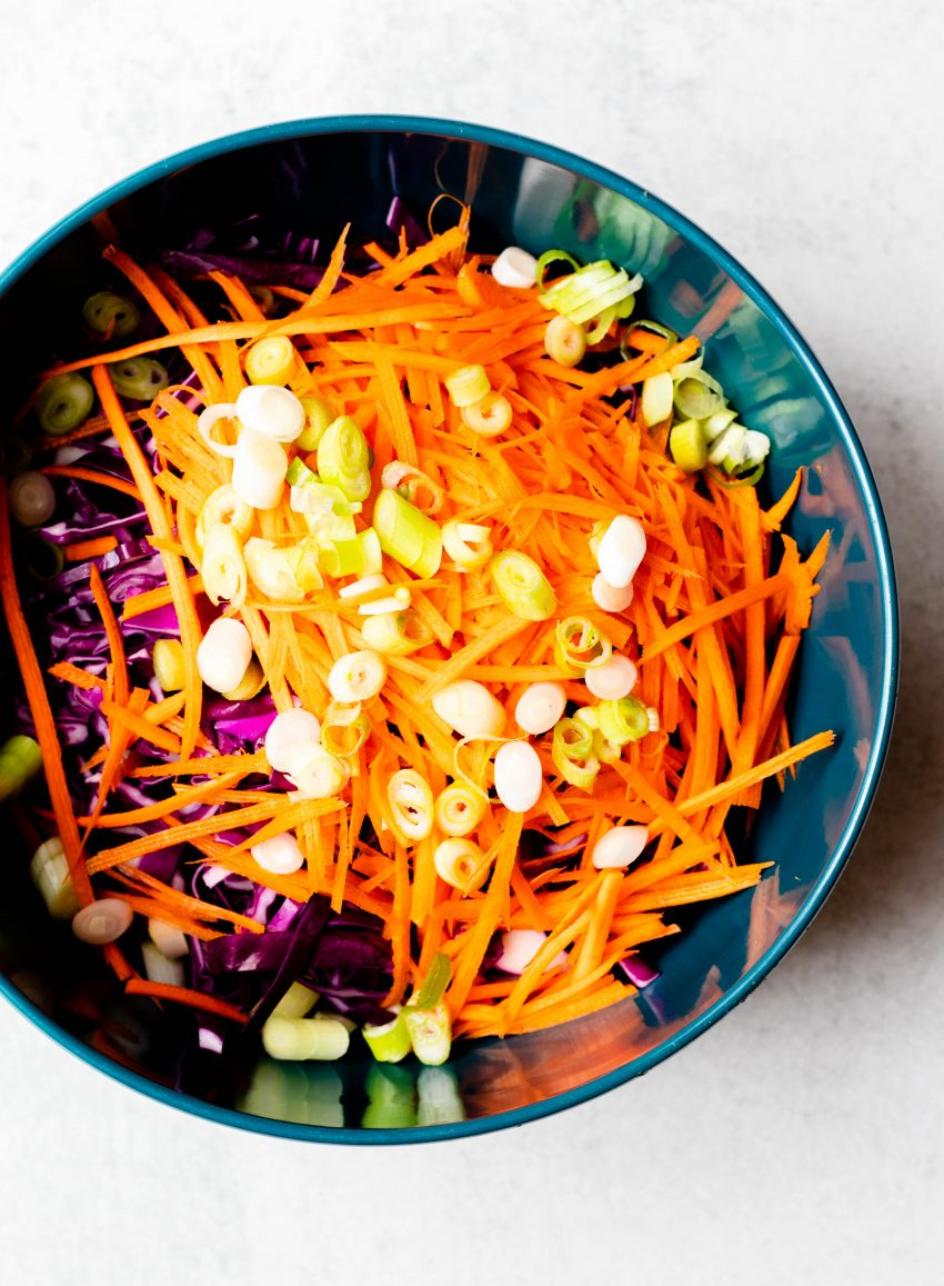 Shredded carrots, scallions, and cabbage in a dark blue mixing bowl