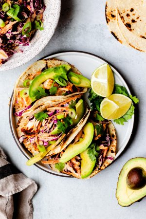 Plate of three grilled salmon tacos with red cabbage slaw with sliced avocado and limes