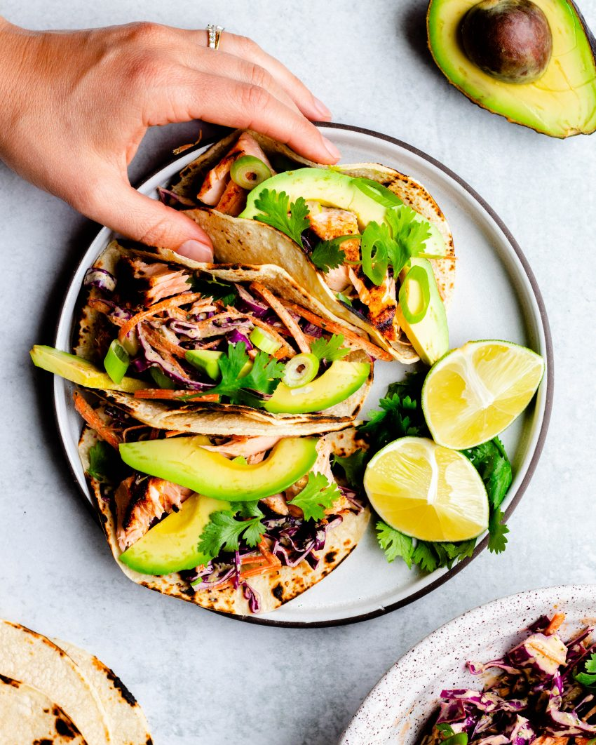 Plate of 3 grilled salmon tacos with a hand grabbing one taco