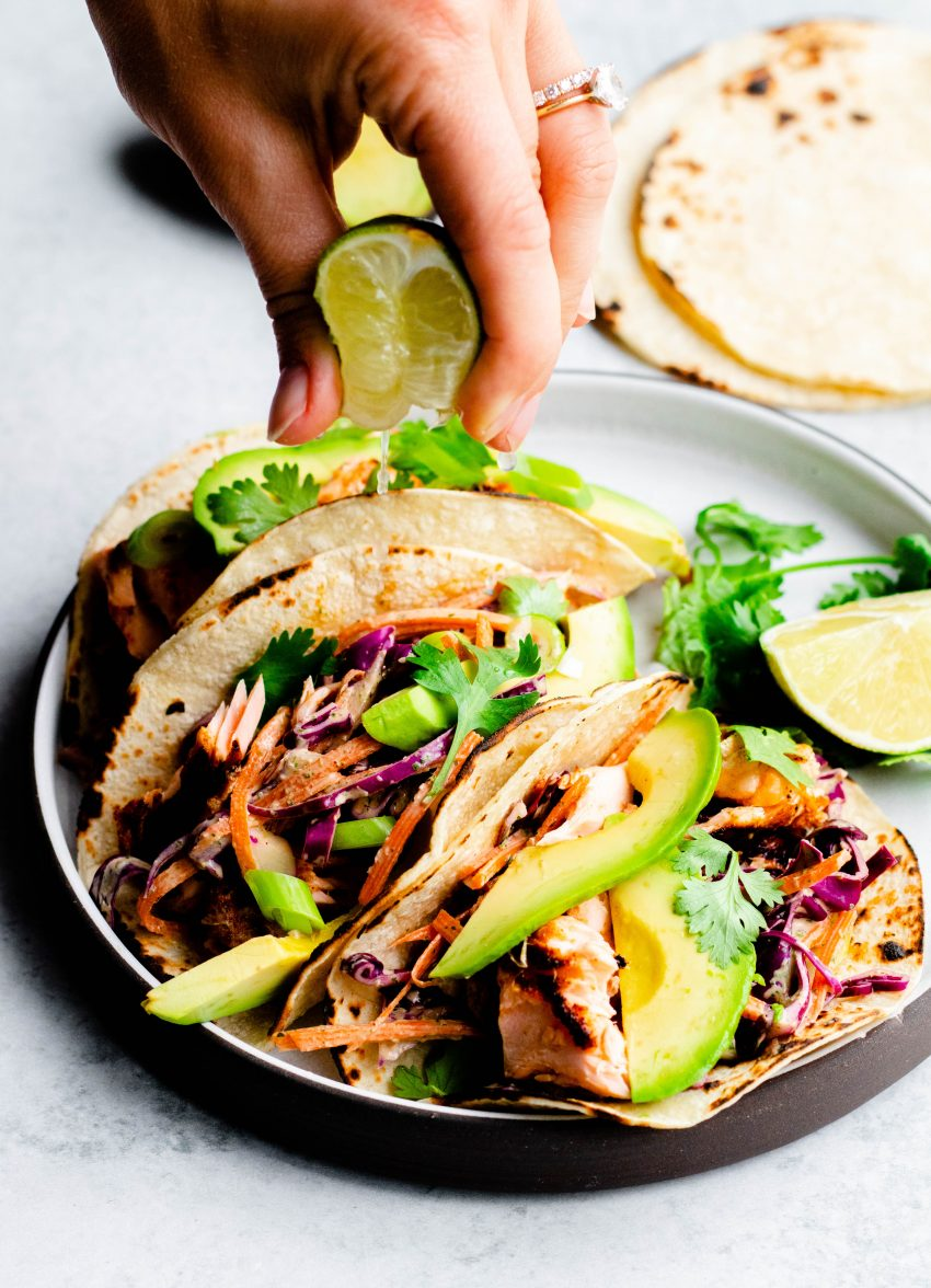 Hand squeezing lime juice onto a plate of 3 grilled salmon tacos
