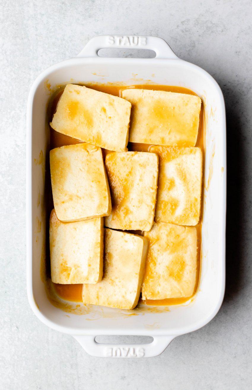 Sliced tofu marinating in a white ceramic dish