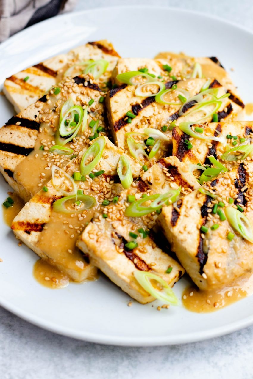 Close up of a plate of miso grilled tofu with chopped scallions, sesame seeds, and miso sesame dressing