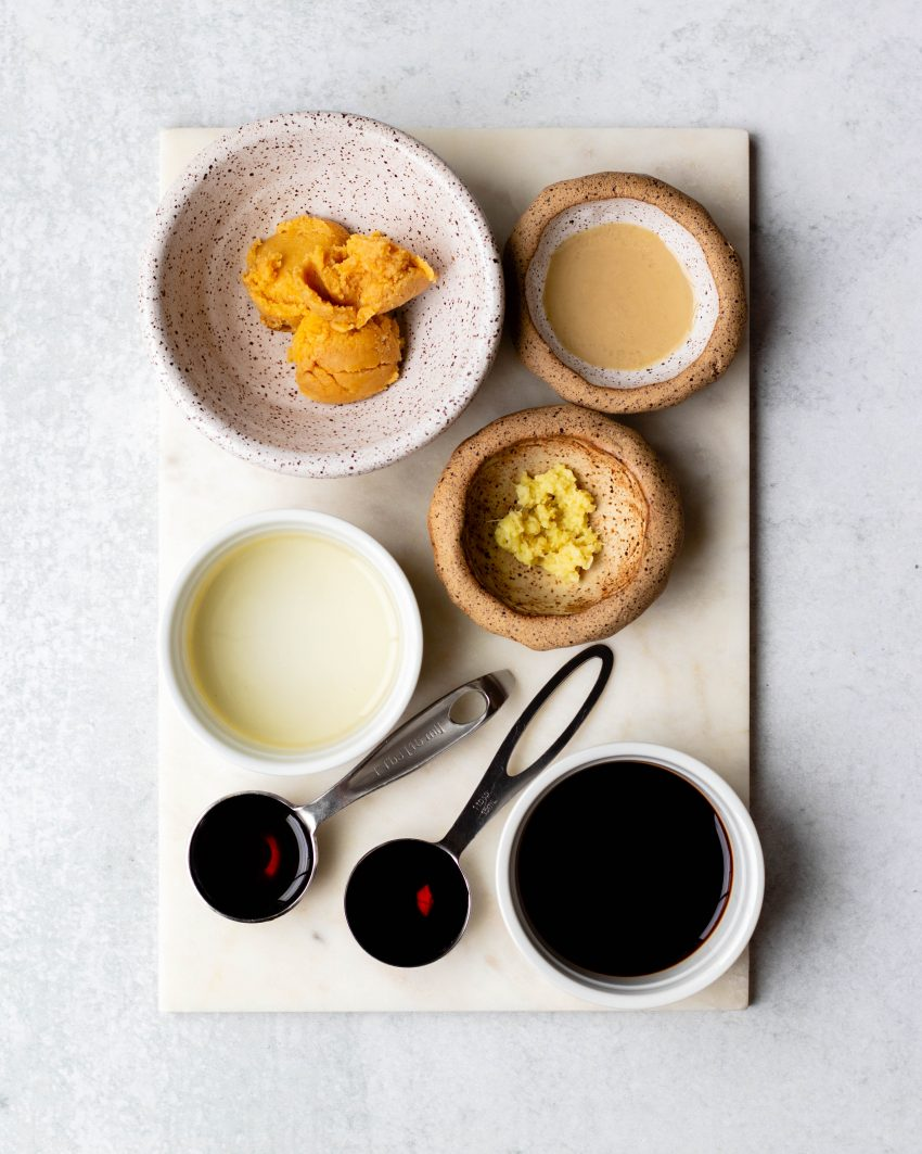 Sesame ginger miso dressing ingredients in measuring utensils on a white board
