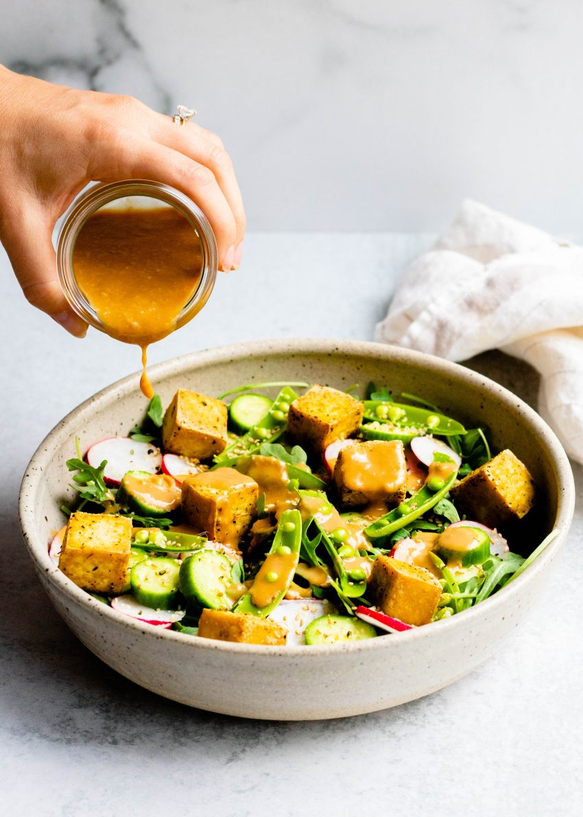 Hand pouring sesame ginger miso dressing onto a salad