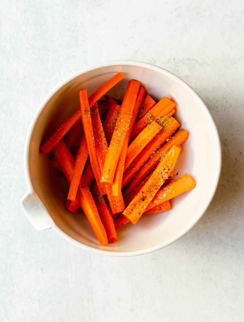 Carrot fries in a mixing bowl before cooking