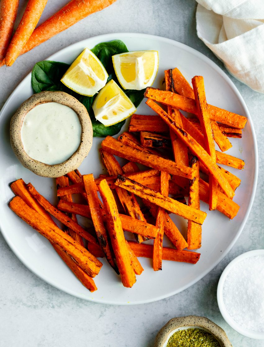 Plate of air fryer carrot fries with tahini dipping sauce, lemon slices, and ingredients surrounding