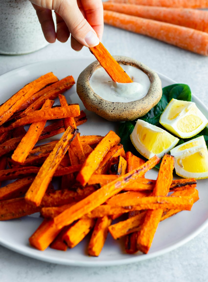Hand dipping carrot fry into lemon tahini sauce