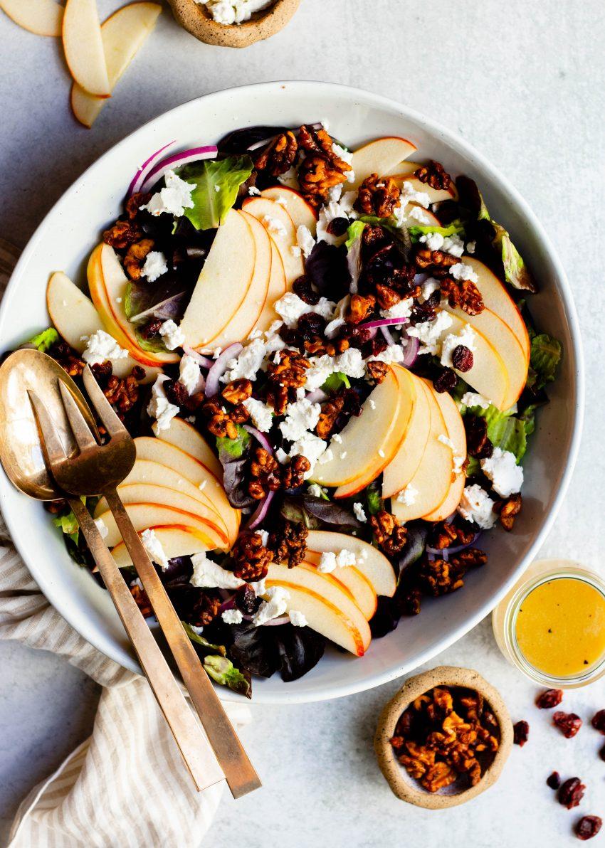 Apple cranberry walnut salad in large salad bowl with gold mixing spoons, surrounded by small bowls of ingredients and salad dressing