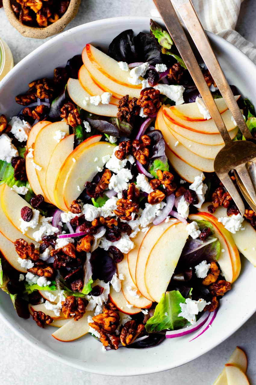 Close up of apple cranberry walnut salad in a bowl with gold serving spoons