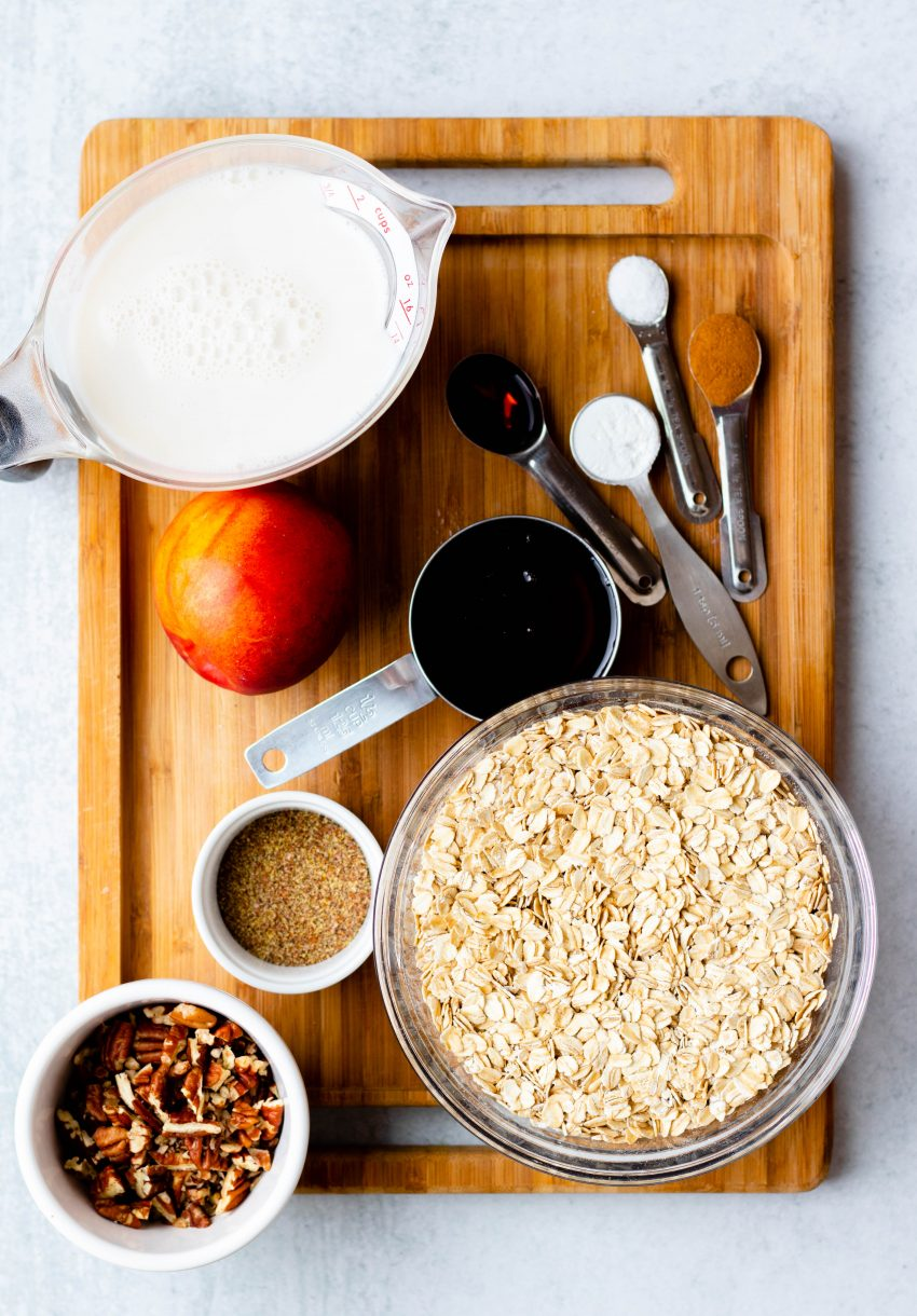 Nectarine baked oatmeal ingredients in bowls and measuring spoons on a wooden board