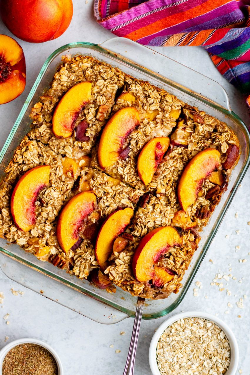 Tray of nectarine baked oatmeal with raw ingredients and a colorful dish towel surrounding
