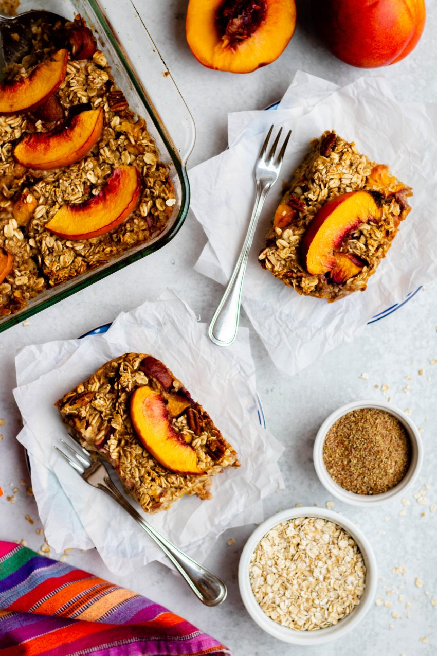 Two slices of nectarine baked oatmeal on plates with ramekins of raw ingredients
