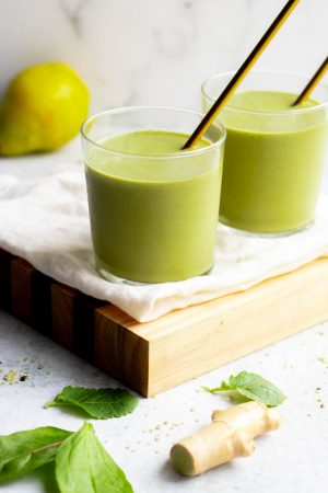 Two glasses of pear banana green smoothie with gold straws sitting on a wooden cutting board