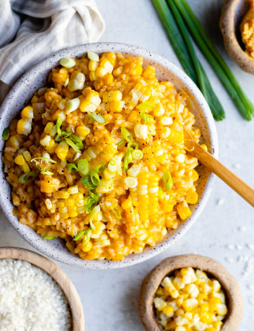 Close up of a bowl of vegan miso corn risotto with a wooden spoon, and small bowls of ingredients surrounding