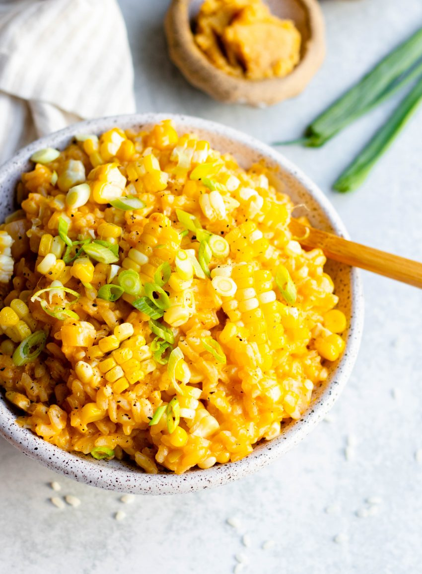 Close up of a bowl of vegan miso corn risotto with a wooden spoon, and bowl of miso paste in the background